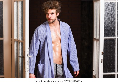 Sexy attractive macho tousled hair coming out through bedroom door. Seductive lover full of desire. Man confident lover near door. Sexy bachelor lover concept. Guy attractive lover posing seductive.