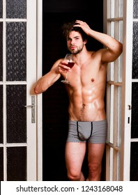 Sexy attractive macho tousled hair coming out through bedroom door. Bachelor sexy body. Sexy lover concept. Guy smooth skin posing seductive. Beginning great evening. Man with sexy torso drink wine.