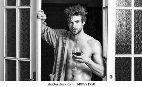 Sexy attractive macho tousled hair coming out through bedroom door. Man with sexy torso drink wine. Sexy lover concept. Bachelor sexy body chest and belly. Guy shimmering sweaty skin wear bathrobe.