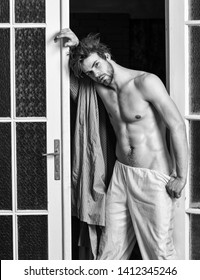 Sexy attractive macho tousled hair coming out through bedroom door. Guy shimmering sweaty skin wear bathrobe. Man athlete with fit sexy torso. Sexy lover concept. Bachelor sexy body chest and belly.