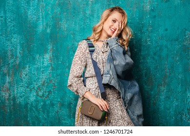 Sexy Attractive Stylish Blonde Woman In Jeans Oversize Jacket Walking Against Vintage Green Wall In Street