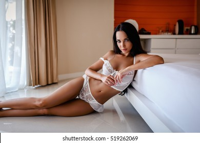 Sexy attractive young brunette woman posing on a bed
