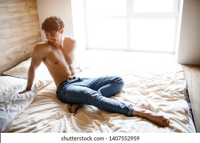 Sexy attractive young man sit on bed and posing on camera. Look back. Alone in room. Daylight. Handsome well-built and slim guy.