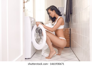 Sexy attractive young woman in white lingerie filling the washing machine crouching down at the open door in her bare feet in a tiled laundry in a side view