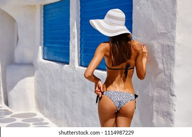 Sexy back of a beautiful tanned slim woman in bikini on white and blue background. Mediterranean architecture style. Sexy model buttocks.