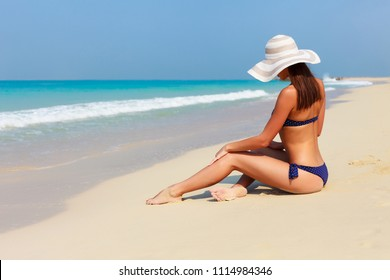 Sexy back of beautiful unrecognizable woman relaxing and sunbathing in bikini on sea background and palm. Sexy buttocks. Beach in Dubai, UAE famous tourist destination