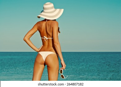 Sexy back of a beautiful woman in bikini on sea background. Sexy buttocks. Retro vintage toned image, film simulation.