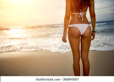 Sexy back of a beautiful woman in bikini on sea background. Sexy buttocks