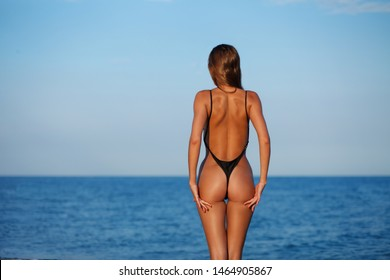 Sexy back of a beautiful woman in black little bikini on sea background. Exotic model at the beach. Sexy buttocks and close up ass. Tanned ideal skin and fit butt. No cellulite, healthy lifestyle
