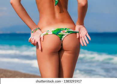 Sexy back of a beautiful woman posing in colorful swimwear bikini at the sea coast. Exotic country travel and rest concept. Slim figure and sexy body.