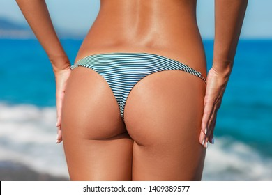 Sexy back of a beautiful woman posing in retro striped swimwear bikini at the sea coast. Exotic country travel and rest concept. Slim figure and sexy body.
