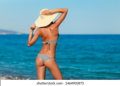 Sexy back of a beautiful woman posing in retro striped swimwear bikini and hat at the sea coast. Exotic country travel and rest concept. Slim figure and sexy body.