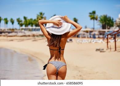 Sexy back of a elegant tanned woman relaxing in bikini on sea background. Sexy buttocks. Ayia Napa, Cyprus island, Mediterranean Sea.