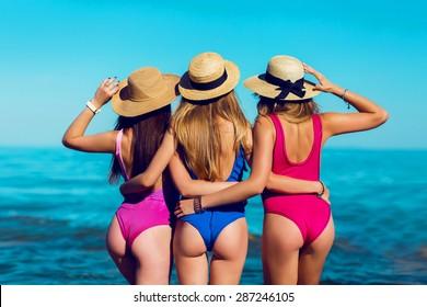 Sexy backs  of three  beautiful women  with perfect body on tropical beach in small  stylish  bikini.