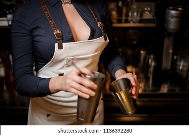 Sexy barmaid with a deep decolletage holding a shaker for making a fresh summer cocktail