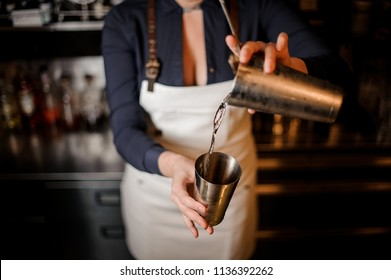 Sexy barmaid with a deep neckline making a fresh summer cocktail in a shaker against the bar