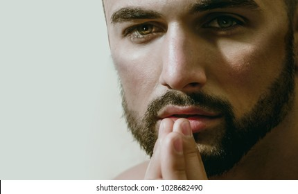 Sexy bearded man looks at camera. Ask for help, trust and eyes. Portrait of young handsome guy with beard, green eyes and naked body. Homosexual or heterosexual young male model topless. Handsome