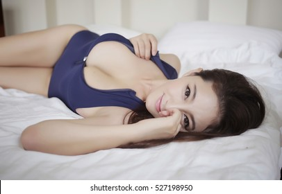 sexy beautiful asian japanese model young lady Pin Up girl flirting lying on bed with big boobs breasts in hotel wearing sexy aerobics dress clothing costumes with body sex pose expose tits boobs