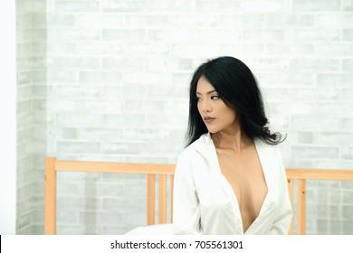 Sexy Beautiful Asian woman wearing white shirt no bra sitting on bed.