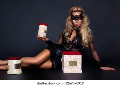 Sexy beautiful blond model in elegant dress holding a gift, flower box with roses. Valentine's gift.