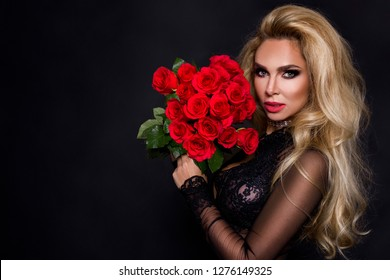 Sexy beautiful blond model in elegant dress holding a bouquet of red roses. Valentines's gift on a black background.