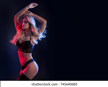 Sexy beautiful blonde in black lingerie isolated on dark background.