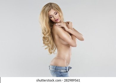 Sexy beautiful blonde woman with perfect body posing almost naked jeanse. Girl with long healthy hair