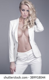 Sexy beautiful blonde woman posing in elegant clothes, looking at camera. Studio shot. Ideal body.