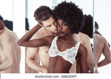 Sexy beautiful brunette african girl in lace underclothes and european handsome men. lingerie model, posing in lingerie in studio, hairstyle, makeup, black and white, sexy