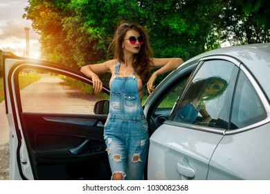 sexy beautiful brunette stands near the white car in denim dress with nude breasts
