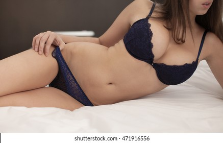Sexy beautiful brunette woman with big boobs lying in bed in sensual blue lingerie