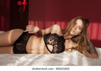Sexy beautiful brunette woman lying in bed in sensual black lingerie, looking at camera.