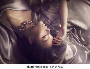 Sexy beautiful brunette woman lying in bed. Sensual woman sleeping in dark room. Natural silk bedlinen, bedclothes.
