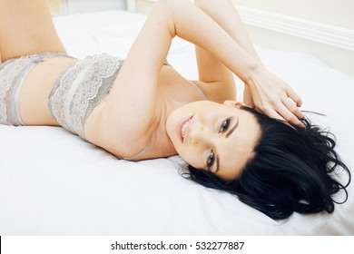 Sexy beautiful brunette woman lying in bed sensual gray lingerie, looking at camera. Seduction concept in luxury room interior