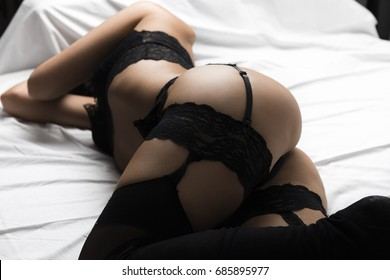 Sexy beautiful brunette woman lying in bed in sensual black lingerie