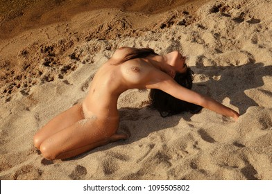 Sexy and beautiful brunette woman naked in the beach next to the river
