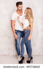 Sexy beautiful couple posing, wearing fashionable jeans. Studio shot. Attractive blonde woman and handsome man.
