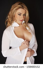 Sexy and beautiful full figured young adult caucasian woman in black lingerie and an open white shirt against a black background