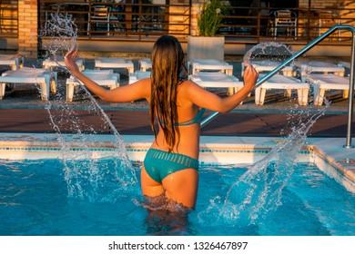 Sexy beautiful girl in knitted bikini having fun in swimming pool at vacation