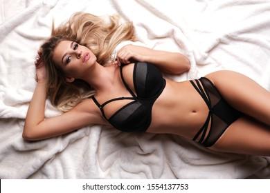 Sexy, schönes Modell in Dessous liegt auf weißem Fell.