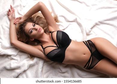 Sexy, beautiful model lying on white fur.