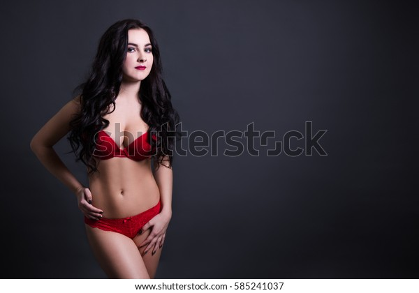 sexy beautiful plus size model in red lace lingerie posing over black background with copy space