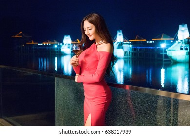 sexy beautiful pretty charming elegant asian Japanese young woman lady grab a glass of wine as hotel dinner wine party banquet guest dressing in formal attire red dress at black night light background