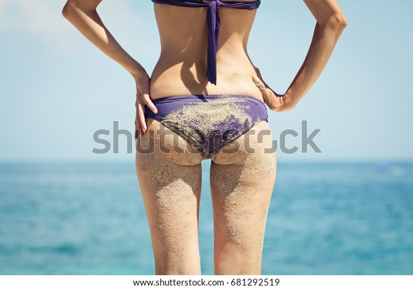 2d160c70444 Sexy beautiful sandy young woman in small bikini with sandy butt (buttocks)  on the