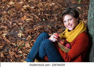 Sexy beautiful smiling romantic girl sitting against a tree eating an apple in the park