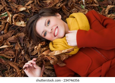 Sexy beautiful smiling romantic girl with short hair leaning down on rusty leaves in autumn day