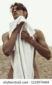 Sexy beautiful striped male model with white towel on the nature background with sand and sky on the beach on the sunset