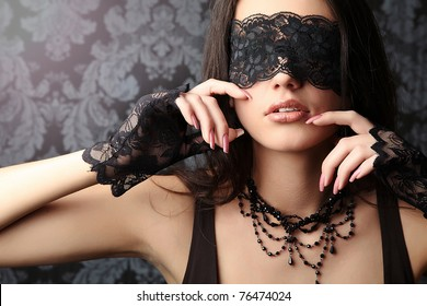 sexy and beautiful  woman with a black lace on her eyes