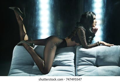 Sexy beautiful woman in a black transparent pantyhose lying on a sofa