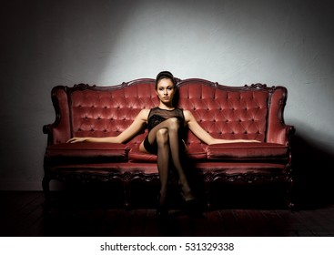 Sexy and beautiful woman in erotic lingerie and stockings posing on a red sofa in vintage interior.